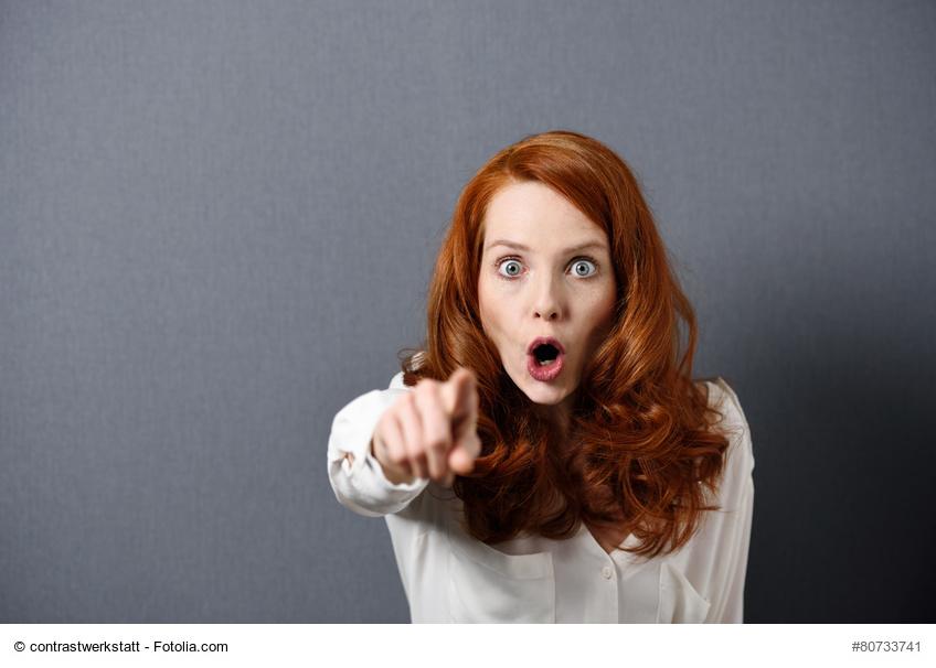 rothaarige Frau deutet mit Finger und schimpft