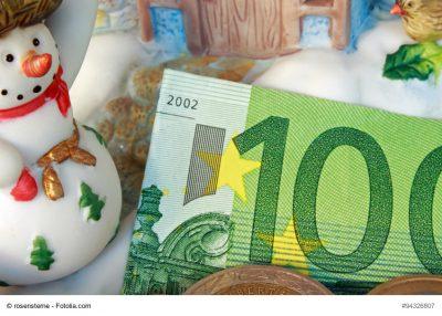 100 Euro- Schein inmitten von Weihnachtsdekoration