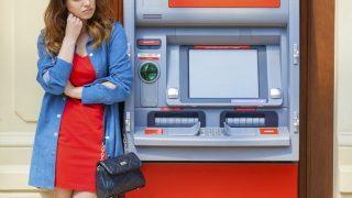 Frau steht ratlos am Bankautomat