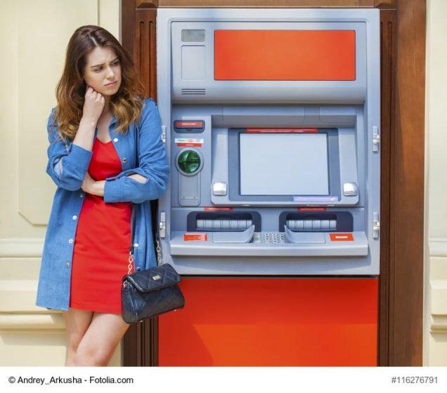 Frau steht ratlos am Geldautomat