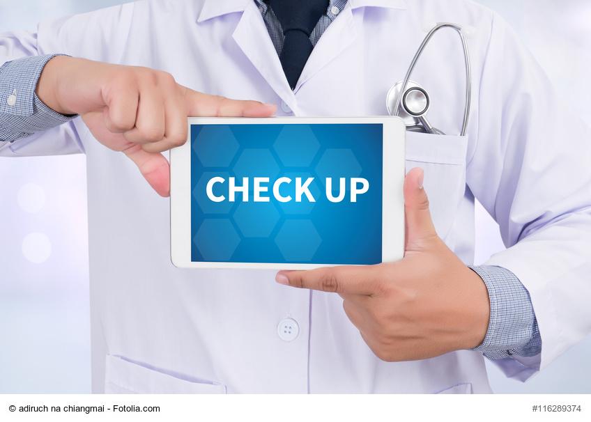 CHECK UP-Schriftzug auf Tablet der von Arzt gehalten wird
