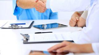 Ärzte im Meeting geben sich die Hand