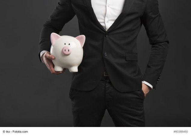 Mann im Anzug trägt großes Sparschwein unter dem Arm
