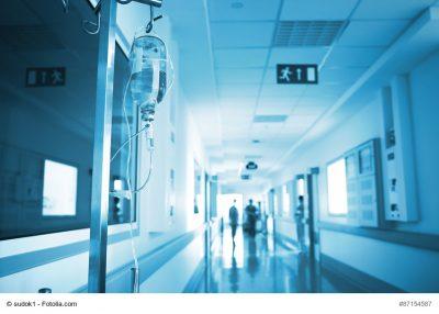 Bett mit Infusion auf Krankenhausflur