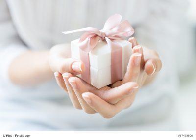 Frau hält Geschenk mir rosa Schleife in der Hand