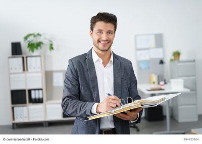 Mann im Büro schreibt etwas in seine Unterlagen