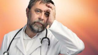 Ärzt hält sich Hand an den Kopf