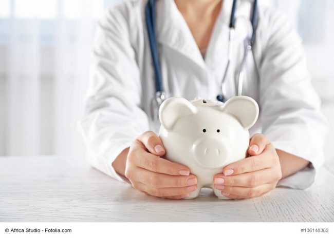 Ärztin hält weißes Sparschwein