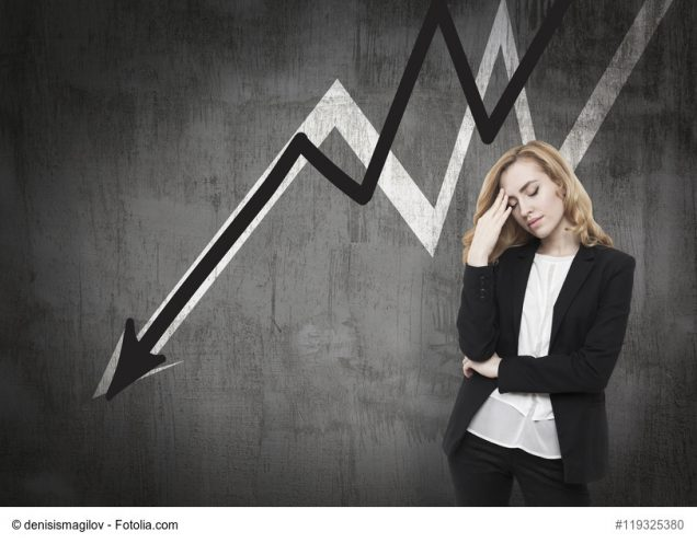 Frau vor Pfeil nach unten blickt gestresst zu Boden