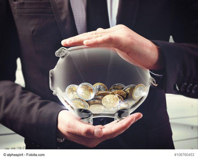 Mann hält gläsernes Sparschwein mit Geld