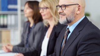 2 Frauen und 1 Mann sitzen in einem Meeting