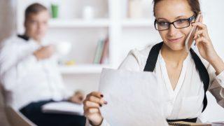 Frau hält Dokument in der Hand und telefoniert