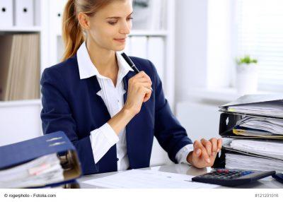 Buchhalterin am Schreibtisch tippt in den Taschenrechner