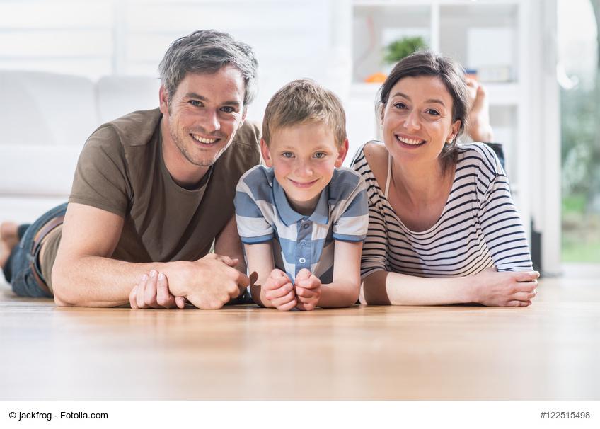 Ehepaar mit kleinem Jungen liegt auf dem Boden im Haus