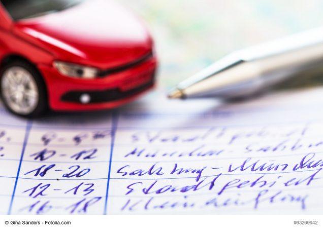Spielzeugauto und Kugelschreiber auf einem Fahrtenbuch