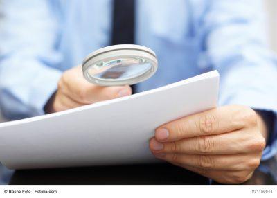 Mann liest Vertrag mit Hilfe von Lupe, Berufsunfähigkeit