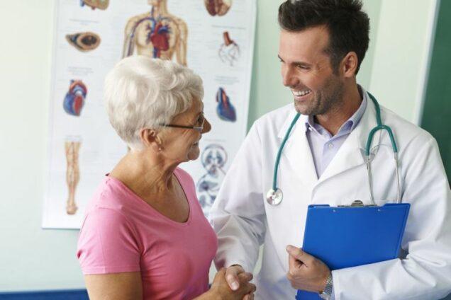 Junger Arzt mit Seniorin in Arztpraxis