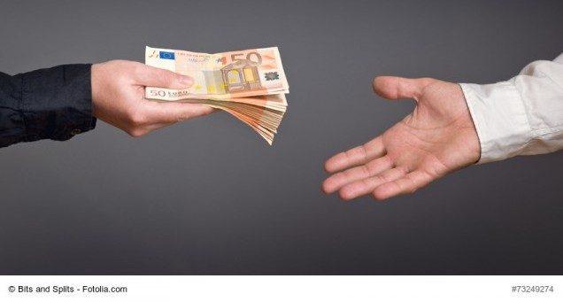Mann reicht anderem Mann ein Geldbündel