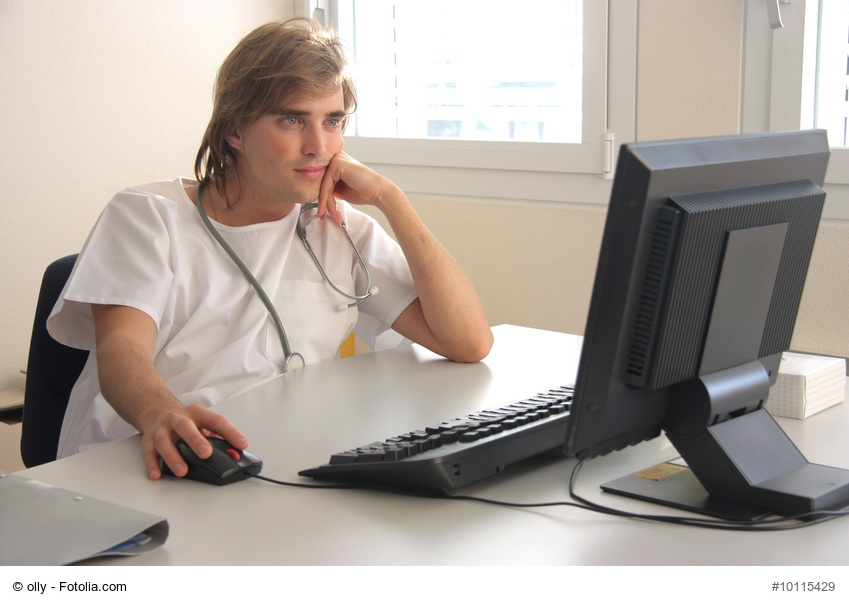 junger Arzt schaut gelangweilt in PC-Monitor