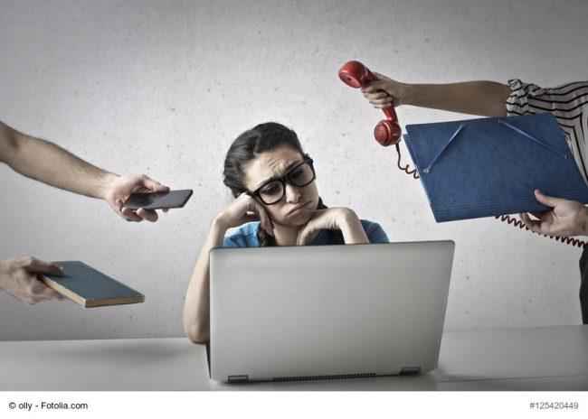 Frau am Laptop wird von Kollegen mit Telefonen und Unterlagen bedrängt