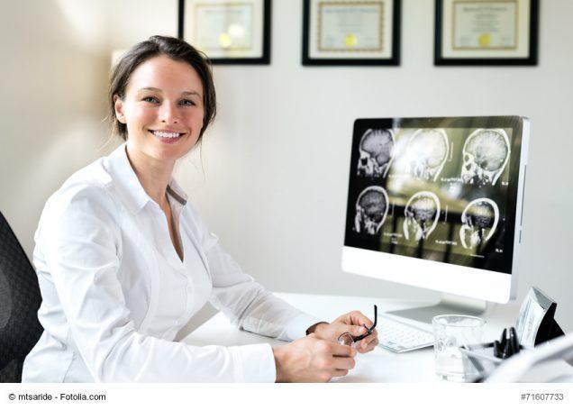 Ärztin vor Bildschirm mit MRT-Ergebnissen
