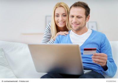 Junges Paar auf Sofa beim Online-Banking