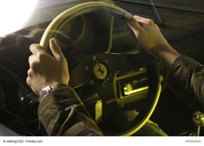 Hände auf dem Lenkrad eines Ferraris