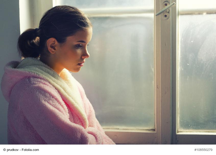 Junges Mädchen im Bademantel sitzt traurig am Fenster