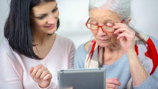 Junge Frau und Seniorin schauen auf ein Tablet