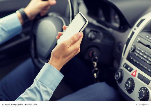 Autofahrer hält Handy in der Hand