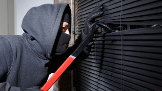 Einbrecher schaut durch Rollo ins Haus