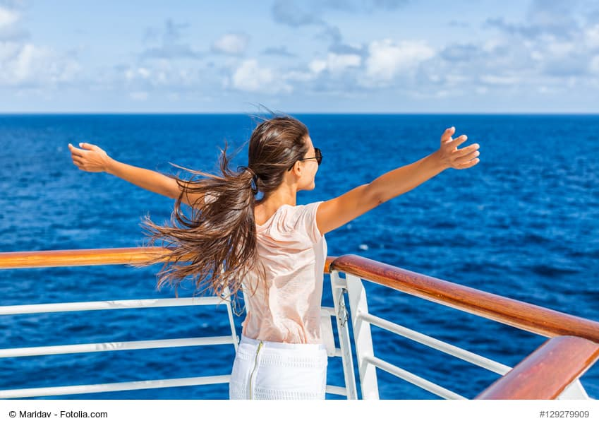 Frau steht an der Reling eines Kreuzfahrt-Schiffs