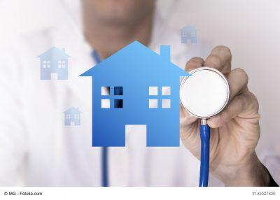 Arzt untersucht mit Stethoskop ein Haus