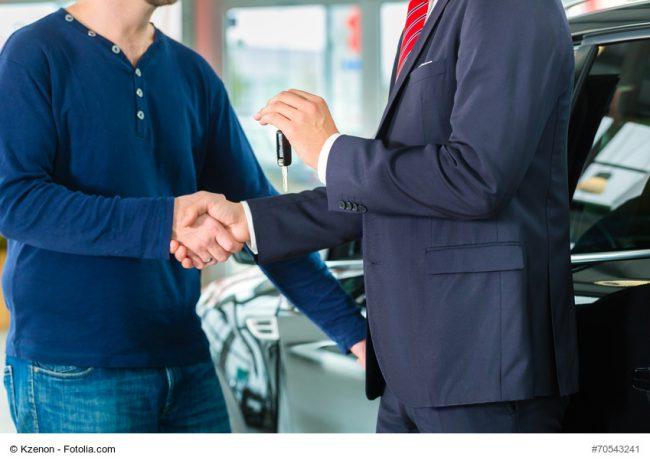 Verkäufer übergibt Autoschlüssel an Kunden