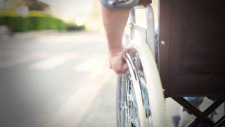Mann im Rollstuhl fährt in Richtung Zebrastreifen