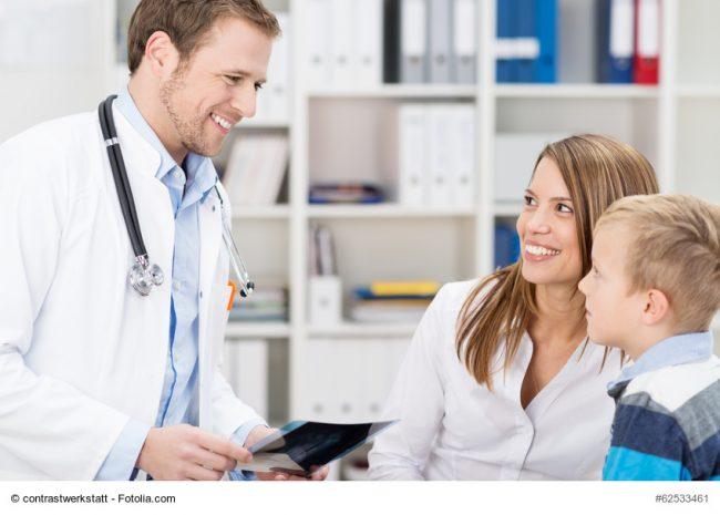 Kinderarzt im Gespräch mit Mutter und Kind in der Arztpraxis