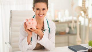 Junge Ärztin am Schreibtisch hält rosa Sparschwein hoch