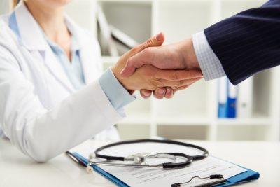 Ärztin gibt Mann im Anzug die Hand