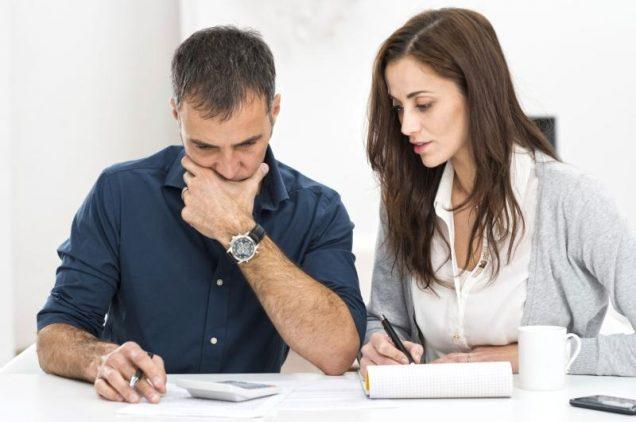 Mann und Frau beugen sich überTaschenrechner und Unterlagen