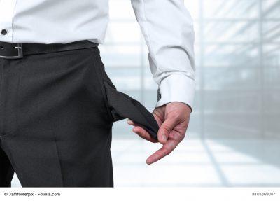 Mann im Anzug zeigt leere Hosentasche als Symbol für Insolvenz