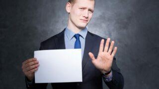 Mann hält Blatt Papier in der Hand und die andere Hand zum Stopp-Zeichen hoch