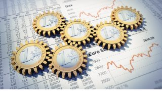 Euromünzen liegen auf Zeitung mit Aktienkurs
