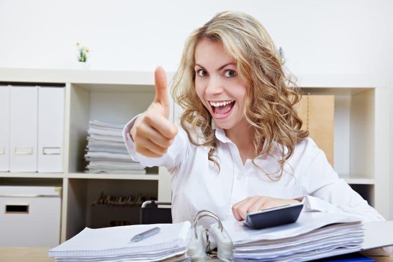 Frau am Schreibtisch reckt Daumen hoch