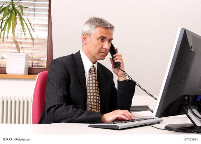 Mann im Anzug sitzt im Büro am Computer und telefoniert