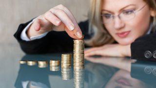Frau stapelt Türme aus Münzen