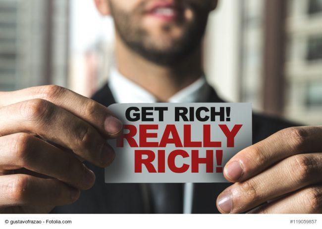 """Mann hät Schild """"get really rich"""" in die Kamera"""