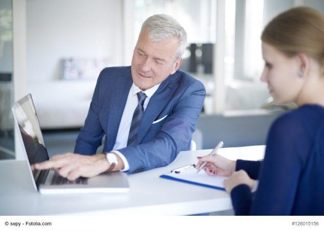 Unternehmer zeigt Mitarbieterin etwas auf Laptop