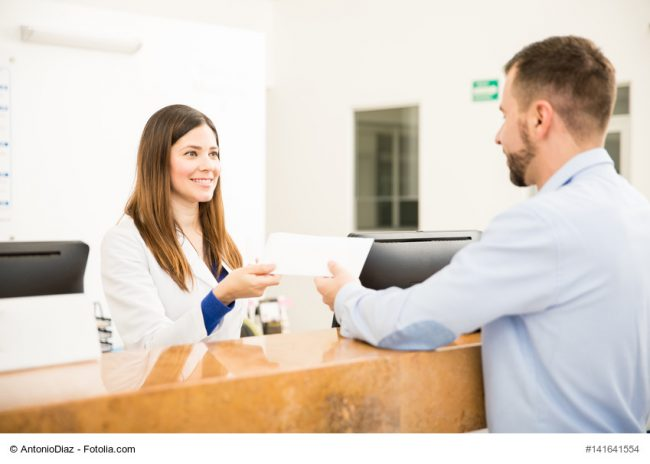 Arzthelferin gibt Patient einen Umschlag