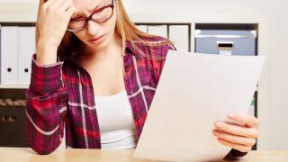 Frau kuckt entsetzt auf Schreiben