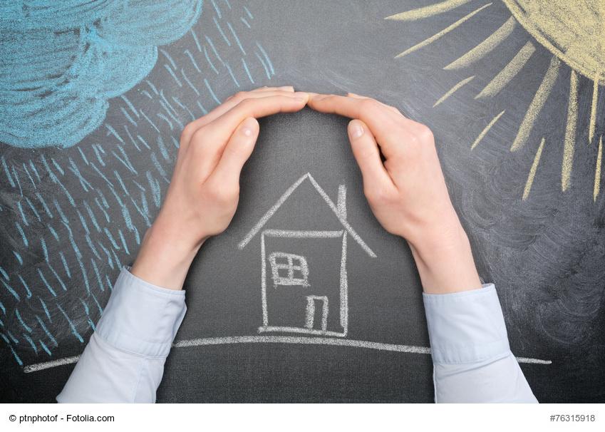 Mann hät schützend Hände über ein gezeichnetes Haus
